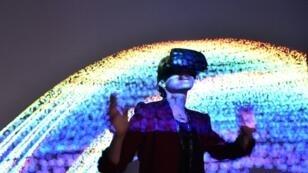 Une visiteuse porte un casque de réalité virtuelle lors de l'exposition Recto VRso du salon Laval Virtual, le 6 avril 2018 à Laval