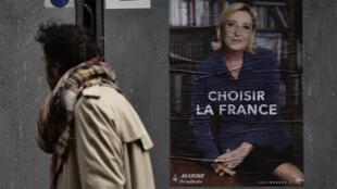 Un piéton passe près d'une affiche de la candidate du parti d'extrême droite Marine Le Pen, à Paris, le 28 avril 2017.