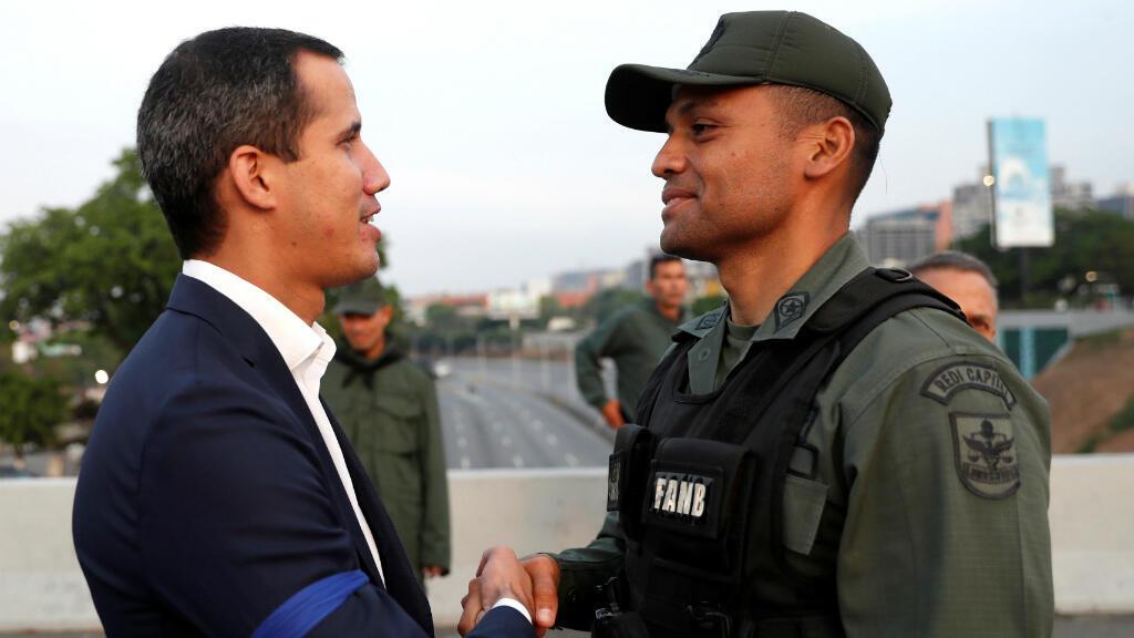 Juan Guaidó saluda a un efectivo militar portando un brazalete azul, símbolo de la rebelión en contra de Maduro el 30A