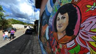 Una mujer con sus hijos pasa el 22 de febrero de 2019 cerca de un mural que representa a la medioambientalista hondureña asesinado Berta Cáceres, en el municipio de Cantarranas, cerca de Tegucigalpa, donde se han pintado casas en su honor antes del tercer aniversario de su muerte el 2 de marzo.