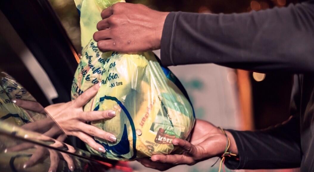 Un grupo de ciudadanos dona alimentos a cientos de venezolanos que intentan regresar por vía terrestre hacia su país, tras perder sus empleos e ingresos, por cuenta de la pandemia del Covid-19. En Bucaramanga, Colombia, el 18 de junio de 2020.