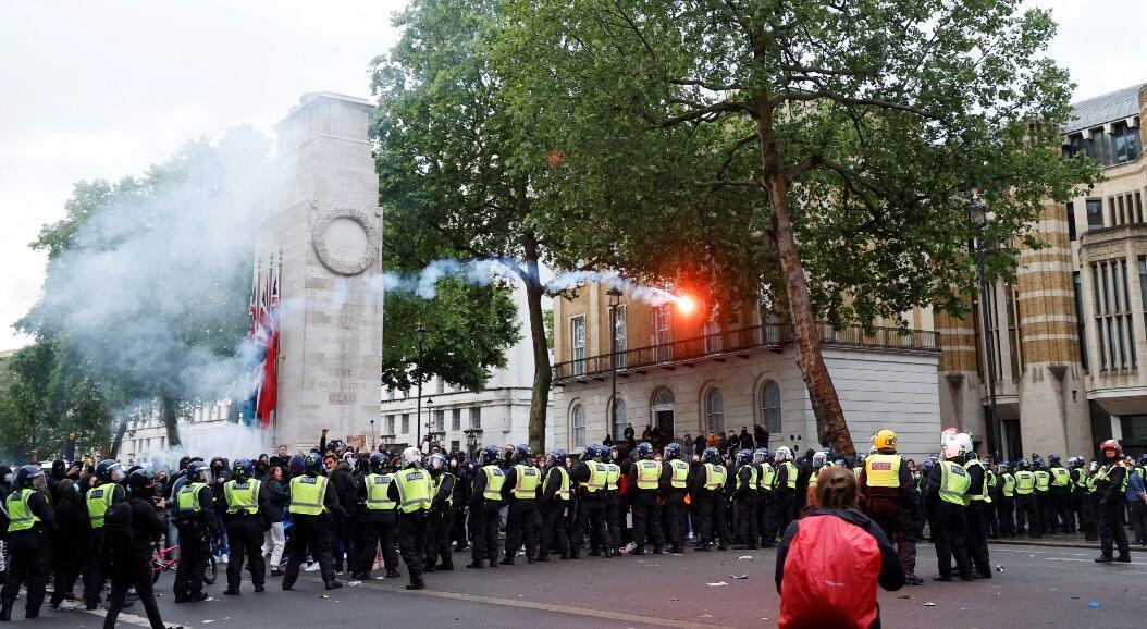 Los oficiales de policía son vistos mientras manifestantes arrojan bengalas en la calle Whitehall, durante una protesta contra el racismo, en Londres, Reino Unido, el 6 de junio de 2020.