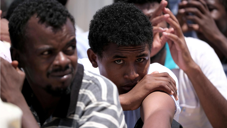 Migrantes sudaneses sentados en el suelo, mientras esperan ser deportados a su país, en el Aeropuerto Internacional de Benina. en Bengasi, Libia, el 8 de agosto de 2019.