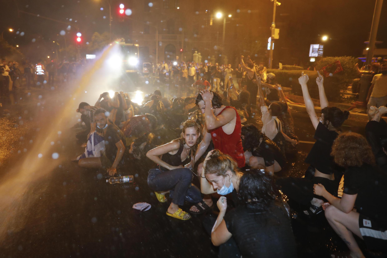 متظاهرون إسرائيليون يواجهون مدافع الماء التي تطلقها الشرطة عليهم في المظاهرات المطالبة رئيس الوزراء الإسرائيلي بنيامين نتانياهو بالاستقالة على خلفية اتهامات بالفساد. 14 يوليو/تموز 2020