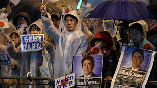 Supporters of the ruling Liberal Democratic Party display posters while waiting for Japan's Prime Minister Shinzo Abe in Tokyo, on October 21, 2017