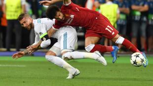 المصري محمد صلاح نجم نادي ليفربول الانكليزي (الى اليمين) يسقط أرضا خلال احتكاك مع لاعب ريال مدريد الاسباني سيرخيو راموس، خلال المباراة النهائية لدوري أبطال أوروبا في كرة القدم، في 26 أيار/مايو 2018.
