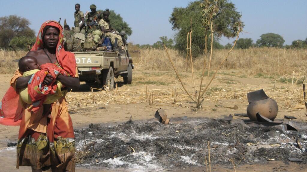 Una mujer lleva a su hijo el 22 de diciembre de 2006 en la aldea de Habile, en el Chad oriental, antes de la llegada del jefe del Alto Comisionado de las Naciones Unidas para los Refugiados (ACNUR), Antonio Guterres. El jefe del ACNUR recorrió los campamentos del Chad oriental en la región de Goz Amir, que albergan a unos 230.000 sudaneses.
