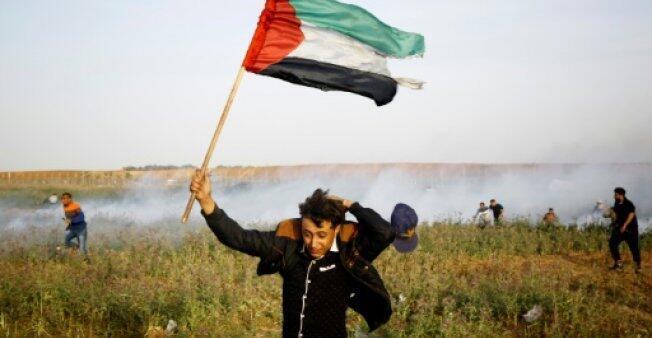 فلسطيني يحمل علما خلال مظاهرة على الحدود بين قطاع غزة وإسرائيل 4 أبريل/ نيسان 2018