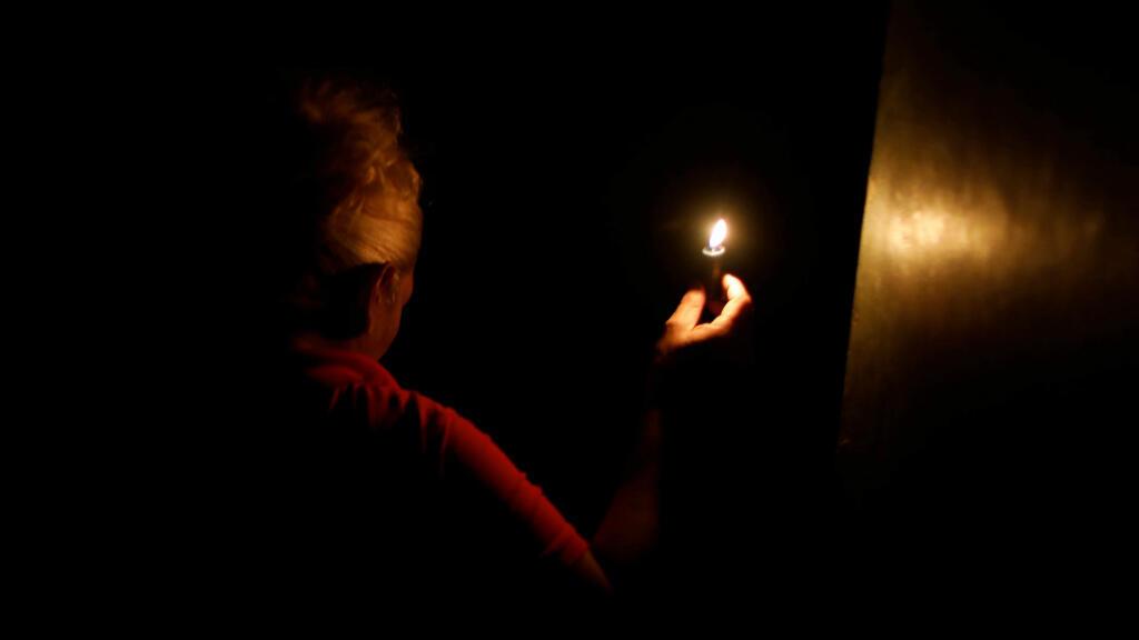 Una mujer usa una vela al entrar en su casa durante el segundo día de apagón en Caracas, Venezuela, el 9 de marzo de 2019.