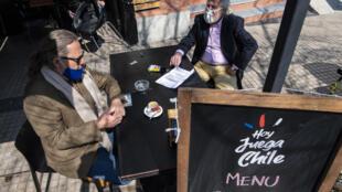 Dos hombres se sientan a la mesa al aire libre de un restaurante durante su reapertura en la comuna Vitacura de Santiago, el 2 de septiembre de 2020