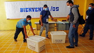 Electoral workers handle boxes containing empty ballot forms to be used by voters at a polling station in a school ahead of the municipal and parliamentary elections in San Salvador, El Salvador, February 27, 2021.
