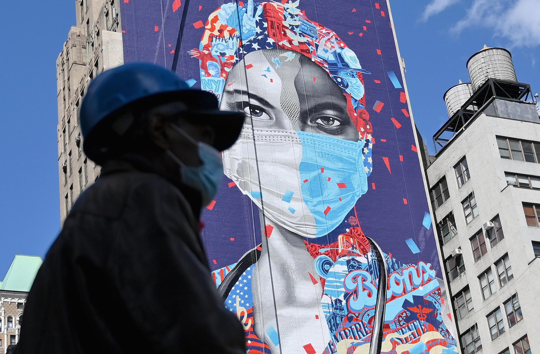 عامل يضع كمامة يمر أمام جدارية تكريمية للطواقم الطبية في نيويورك في 7 مايو/أيار 2020.