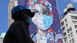 عامل يضع كمامة يمر أمام جدارية تكريمية للطواقم الطبية في نيويورك في 7 أيار/مايو 2020