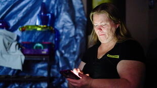 """Christina Beverly checks her phone in the dark after winter weather caused electricity blackouts and """"boil water"""" notices in Fort Worth, Texas, U.S. February 20, 2021."""