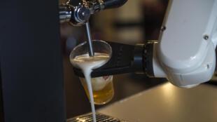 El robot-camarero fabricado por la empresa española Macco Robotics, sirve una cerveza en el bar 'La Gitana Loca' de Sevilla el 17 de mayo de 2020