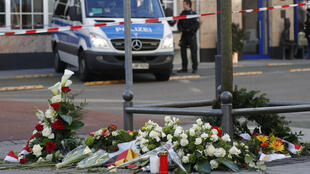 A police car is seen behind flowers placed at a makeshift memorial for the victims of the Hanau shooting in front of a shisha bar in Hanau near Frankfurt am Main, western Germany, on February 21, 2020. - Thousands of people took part in vigils across Germany on February 20, 2020, after a gunman with apparent far-right beliefs killed nine people at a shisha bar and a cafe in the city of Hanau on February 19, 2020. The suspect, a 43-year-old German, was found dead at his home after the rampage along with his 72-year-old mother in what appeared to be a murder-suicide.
