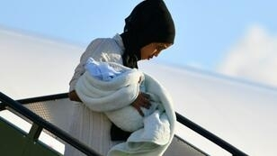 A Libyan mother and child disembark at the Pratica di Mare military airport, on the outskirts of Rome
