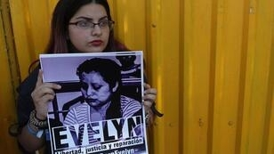 Miembro del colectivo Agrupación ciudadana para la despenalización del aborto con un cartel sobre el tema.