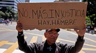 """Un hombre sostiene una pancarta que dice """"No más injusticia. Hay hambre"""" durante una protesta de jubilados por su pensión en Caracas, Venezuela , el 1 de septiembre de 2018."""