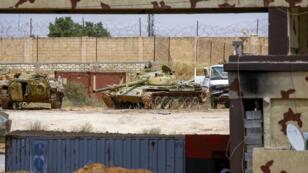 Un tank et un véhicule de transports de troupes dans un camp qu'utilisaient les forces pro-Haftar à Gharian, le 28 juin 2019.
