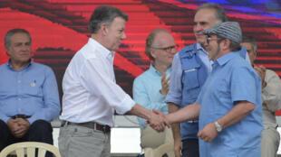 El presidente Juan Manuel +Santos y el líder de la exguerrila de las Farc, alias 'Timochenko' se dan la mano durante ceremonia de desmovilización. 27 de junio de 2017.