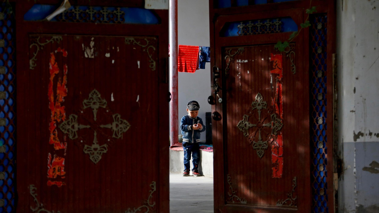 En esta foto del 20 de septiembre de 2018, un niño uigur juega solo en el patio de una casa en la Unidad Nueva Aldea en Hotan, en la región occidental de Xinjiang, China.