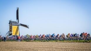 Le peloton passe devant un moulin à vent durant l'Amstel Gold race le 21 avril 2019 aux Pays-Bas