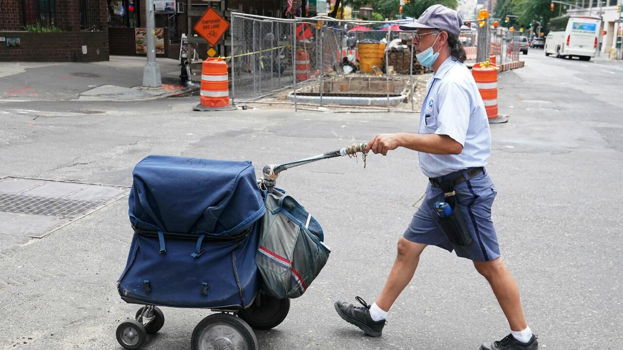 Un trabajador del Servicio Postal de EE. UU. camina con su carrito en el distrito de Manhattan de la ciudad de Nueva York, EE. UU., el 30 de julio de 2020.