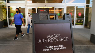 Women wearing facemasks exit a shopping mall where a sign is posted at an entrance reminding people of the mask requirement Westfield Santa Anita shopping mall on June 12, 2020 in Arcadia, California