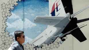 Un homme passe devant une fresque représentant le vol MH370, dans la ville malaysienne de Shah Alam.