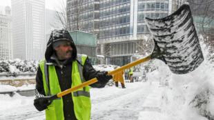 Un trabajador intenta reducir la alta capa de nieve que cayó en la Avenida Michigan de la ciudad de Chicago