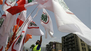 Un vendeur à la sauvette écoule des drapeaux libanais et chrétiens à Beyrouth.