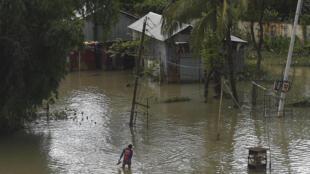 رجل يسير في مياه الفيضانات في سونامغونغ ببنغلادش في 14 تموز/يوليو 2020