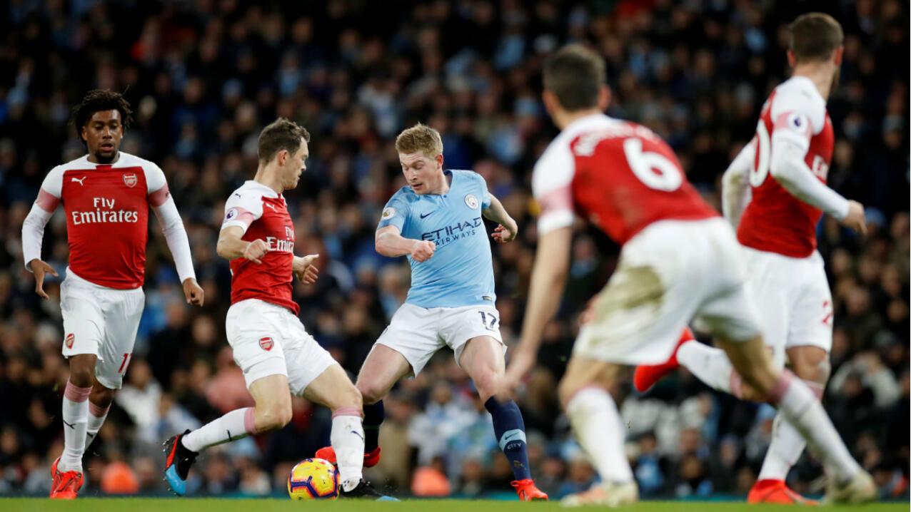 El jugador belga, Kevin De Bruyne, del Manchester City, se enfrenta contra otros futbolistas, entre ellos, el suizo, Stephan Lichtsteiner, del Arsenal, en el Etihad Stadium, Manchester, Reino Unido, el 3 de febrero de 2019.