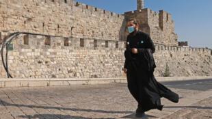 Un sacerdote con mascarilla camina junto a los muros de la Ciudad Vieja de Jerusalén, el 12 de septiembre de 2020