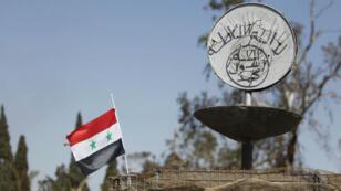 Le drapeau syrien flotte à côté d'un slogan de l'EI à Palmyre, en avril 2016.