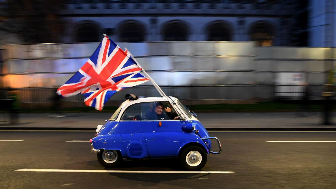 Un homme agite des drapeaux du Royaume-Uni depuis une petite voiture à proximité de partisans du Brexit rassemblés sur la place du Parlement, à Londres, le 31 janvier 2020.