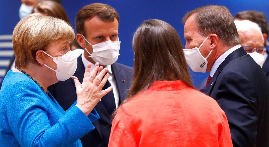 La canciller alemana, Ángela Merkel, habla con el presidente de Francia, Emmanuel Macron, el primer ministro de Finlandia, Sanna Marin, y el primer ministro de Suecia, Stefan Lofven, durante la cumbre de la Unión Europea, en Bruselas, Bélgica, el 18 de julio de 2020.