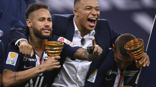 PSG players Neymar (L), Kylian Mbappé (C) and Marco Verratti celebrate after the team's victory against Lyon in the French League Cup final at the Stade de France on July 31, 2020.