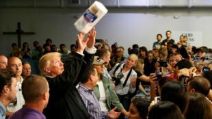 El presidente Donald Trump lanza rollos de papel  a la gente afectada por el huracán en un centro de socorro en la capilla de San Juan, Puerto Rico. Octubre 3, 2017.