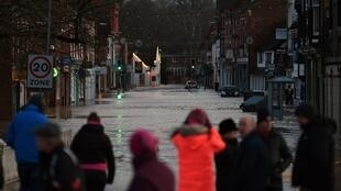 People look at flood water in a flooded street in Tenbury Wells, after the River Teme burst its banks in western England, on February 16, 2020,