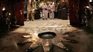 Fransciscan priests pray during a procession in front of the Bethlehem star inside the Grotto at the Church of the Nativity, in the West Bank town of Bethlehem on December 18, 2014