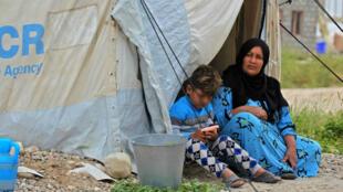 Une femme et un garçon assis à l'entrée d'une tente dans le camp Laylan, à 25km de la ville irakienne de Kirkouk, le 9 mai 2019.