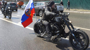 """Dmitry Serebryakov, AFP I Alexander Zaldostanov also known as """"Khirurg"""" (The Surgeon), leader of the Night Wolves bikers' club, rides in Moscow on April 25, 2015, at the beginning of a ride through Europe"""