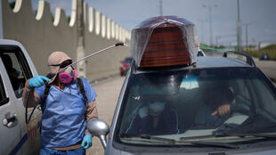 """A worker sprays disinfectant on a vehicle carrying a coffin lined up to enter a cemetery as Ecuador's government announced on Thursday it was building a """"special camp"""" in Guayaquil for coronavirus disease (COVID-19) victims, in Guayaquil, Ecuador, on April 2, 2020."""