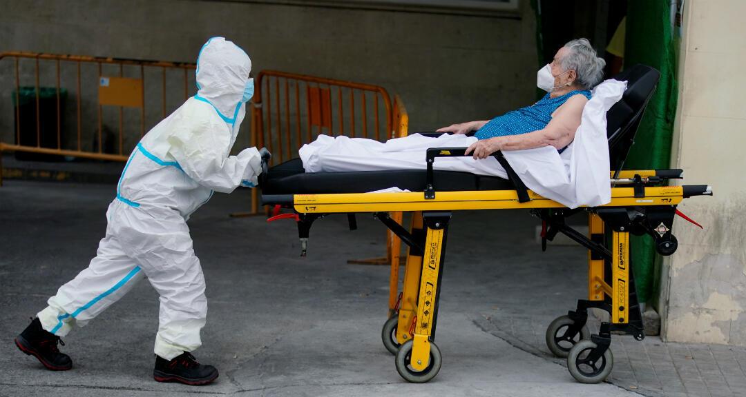 Un equipo de protección empuja una camilla con un paciente durante el brote de coronavirus en Madrid, España, el 10 de agosto de 2020.