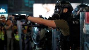 Un manifestante antigubernamental increpa a la policía y desafía la ley anti-máscaras. 20 de octubre de 2019.