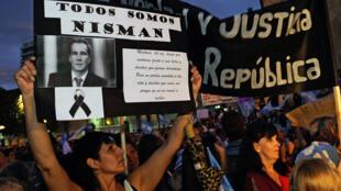 Una mujer sostiene un cartel con el retrato del fiscal Alberto Nisman en Rosario, Argentina, el 18 de febrero de 2015, durante una marcha simultánea a la Marcha del Silencio convocada por los fiscales argentinos en memoria de su difunto colega Alberto Nisman en Buenos Aires.