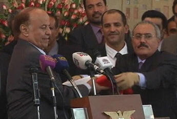 Ousted Yemeni president, Ali Abdullah Saleh, hands over the flag to newly inaugurated President Abd-Rabbu Mansour Hadi.