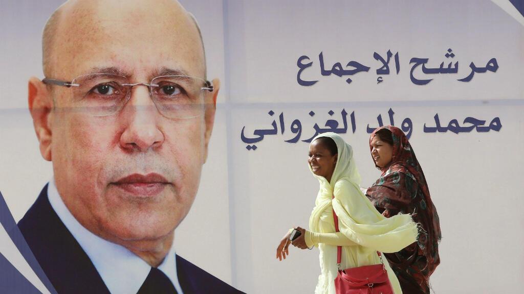 Mujeres caminan junto a un cartel electoral del candidato presidencial oficialista Mohamed Ould Ghazouani en una calle de Nuakchot, Mauritania, el viernes 21 de junio de 2019.